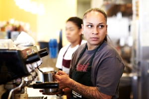 Homegirl Cafe worker, woman making espresso, tattoos