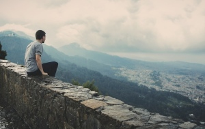 man sitting on wall enjoying view of city below