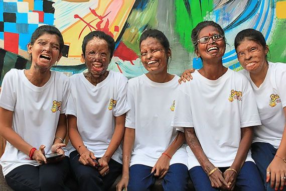 the staff of Sheroes Hangout in Agra, India, sit in front of mural