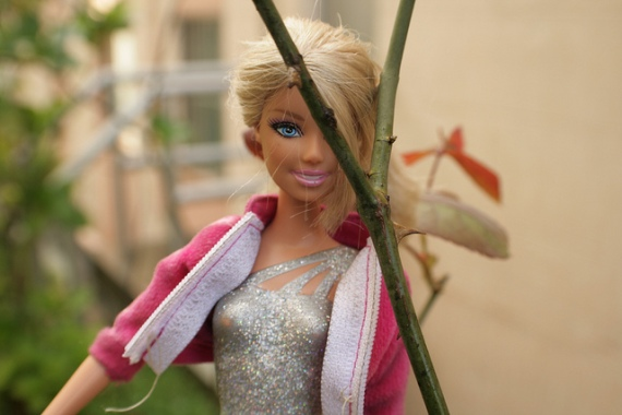 Barbie doll behind rose stems